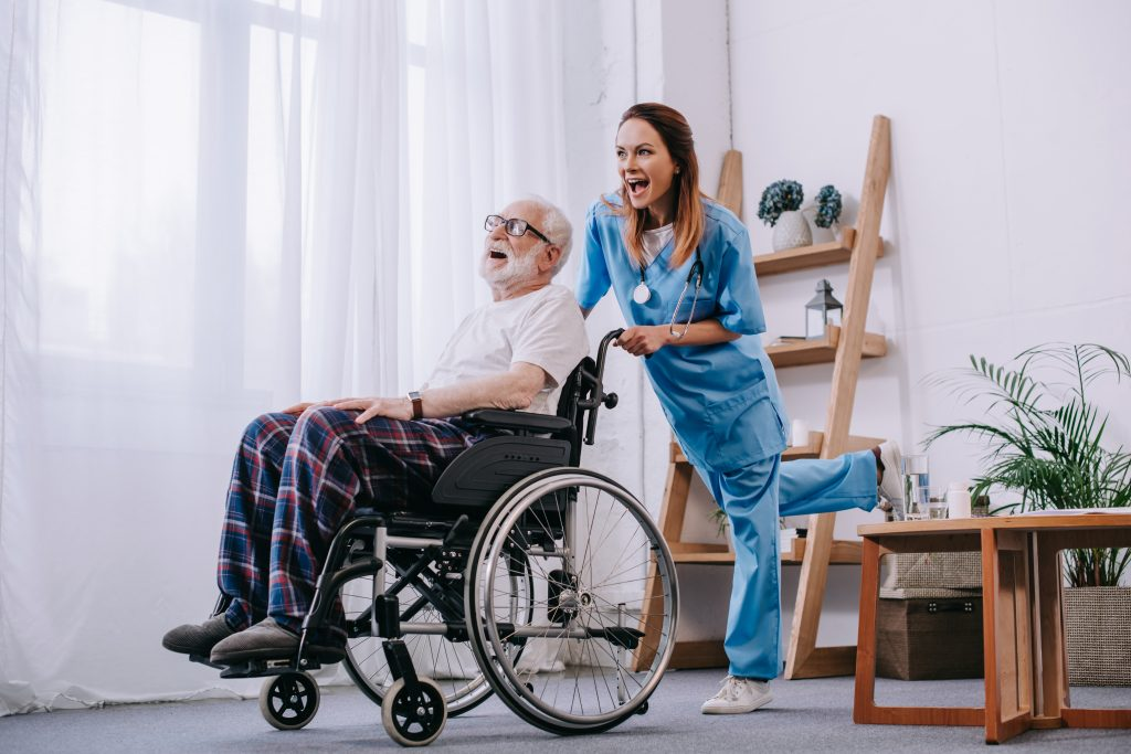 happy nurse at 360Care with patient in wheelchair